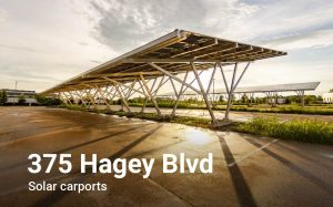 """Perspective corrected fisheye photo of a giant pair of solar carports at sunset. The structures are backlit, casting shadows across the wet tarmac of the surrounding parking lot. Text over photo says, """"375 Hagey Blvd solar carports."""""""