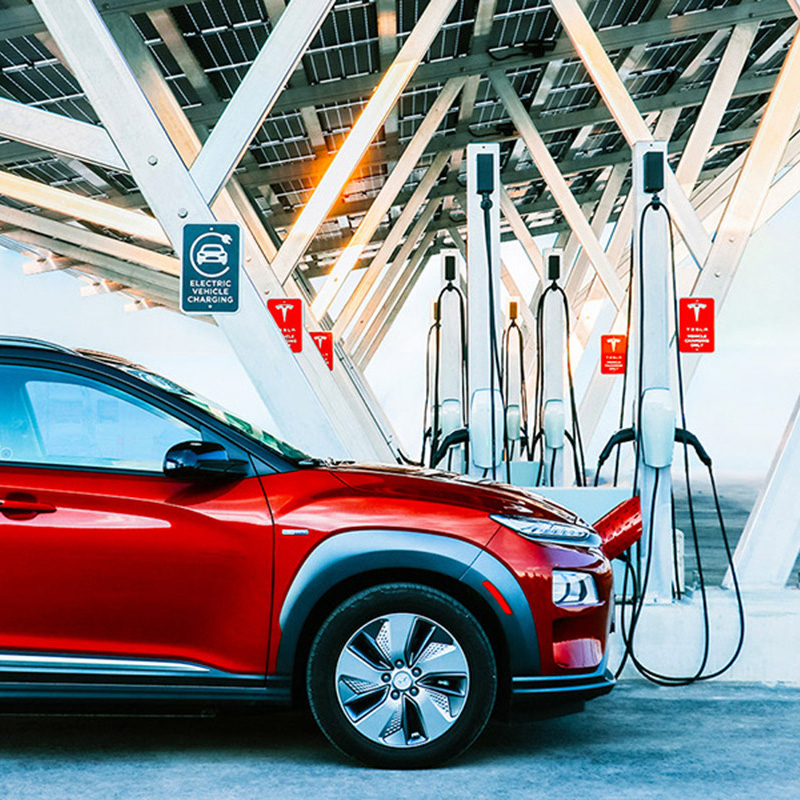A red electric SUV under a solar carport, parked next to Tesla EV chargers.