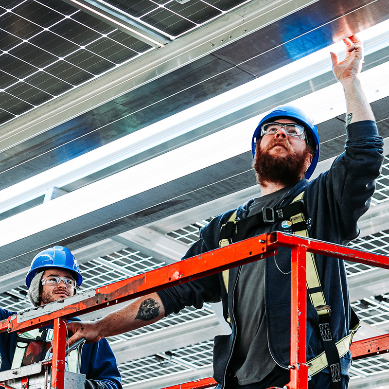 Solar technicians inspecting and installing solar panels. Shot fro m below, the technicians are working at heights in a hydraulic lift.