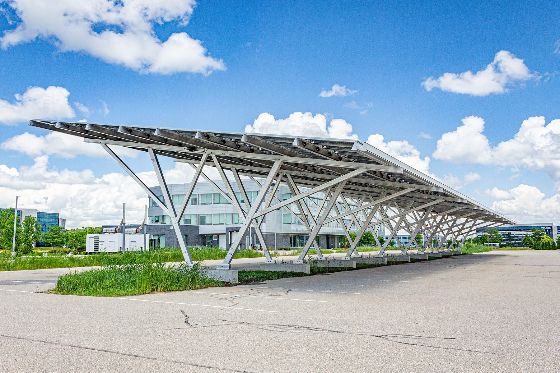 Solar Carport at 375 Hagey Blvd, WaterlooONtario. Carport is photographed against a fair weather sky with sun and puffy white closu